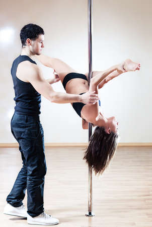 poledance: Pole dance trainer. Young man training woman.