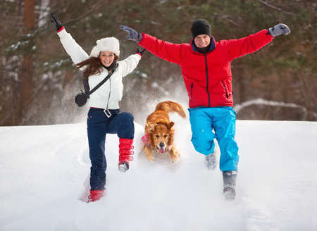 Young couple with dog winter outdoors fun. Stock Photo - 9122333