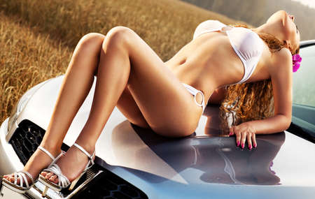 Young sexy woman on car hood.