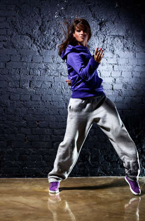 hip hop dancer: Young woman dancer. On wall background.