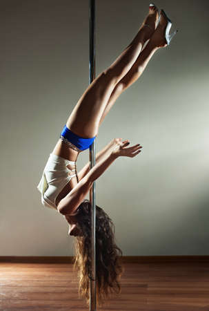Young slim pole dance woman. On wall background. photo