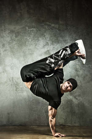 break dancer: Young strong man break dance. On wall background. Stock Photo