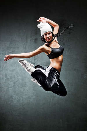 Young woman dancer jumping. On wall background. Stock Photo