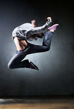 hip hop dancer: Young woman dancer jumping. On wall background. Stock Photo