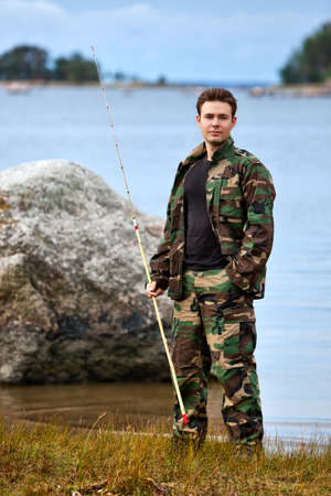 Young male fisher on lake shore. Stock Photo - 9353580