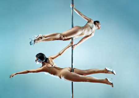 Two young sexy pole dance women. Stock Photo - 9463369