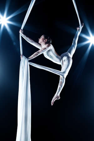 Young woman gymnast. On black background with flash effect. Stock Photo - 9493379