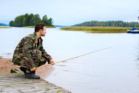 Young male fisher on lake shore. Stock Photo - 9668868