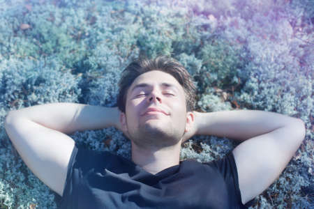 Young man resting on grass in forest. Stock Photo - 9689518