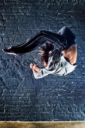 alto rendimiento: Bailarina joven saltando. El fondo de la pared.