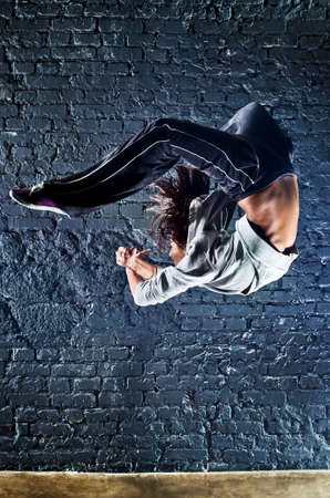 high jump: Young woman dancer jumping. On wall background. Stock Photo