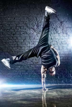 danse contemporaine: Jeune homme fort break dance. Sur fond sombre mur.
