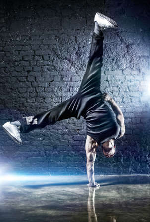 contemporary dance: Young strong man break dance. On dark wall background.