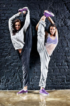 Two women dancers. On wall background. photo