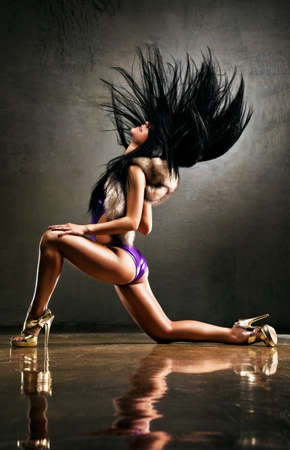 Young sexy woman dancing on wall background. photo