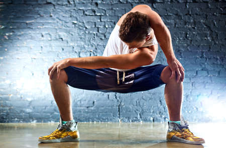 Young man sports exercises. On wall background. photo