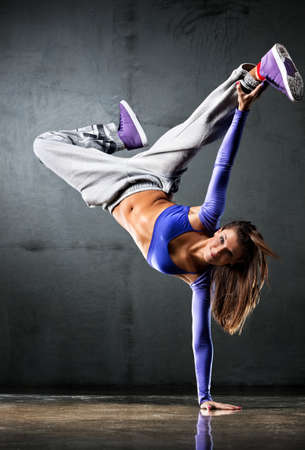 hip hop dancer: Young woman dancer on wall background.
