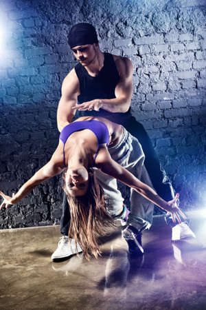 hip hop dance: Dancer couple. On wall background.