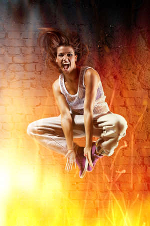 Young woman dancer jumping. With fire effect. photo