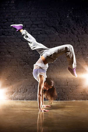 hip hop dance: Young woman dancer on wall background.