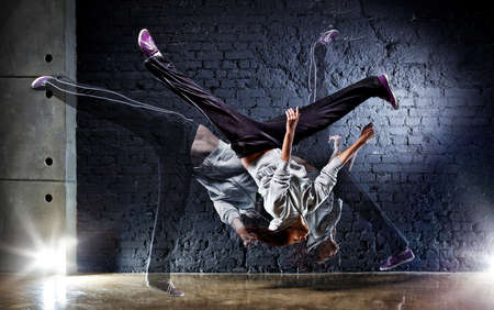 hip  hop: Young woman dancer on wall background.