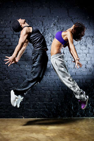 hip hop dancing: Young dancer couple jumping. On wall background.