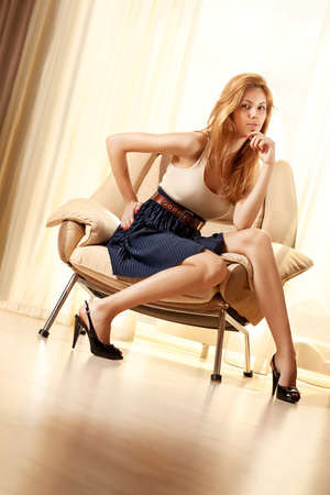 Young woman sitting on chair in modern interior. photo
