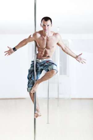 poledance: Young strong pole dance man.