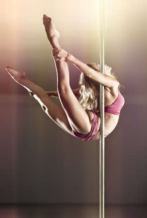 poledance: Young pole dance woman. On wall background.