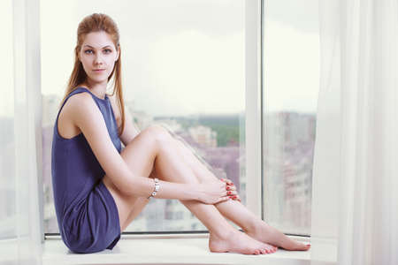 Young woman sitting in front of window. Stock Photo - 10117245