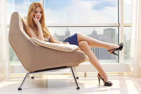 Young woman sitting on chair on window background. photo