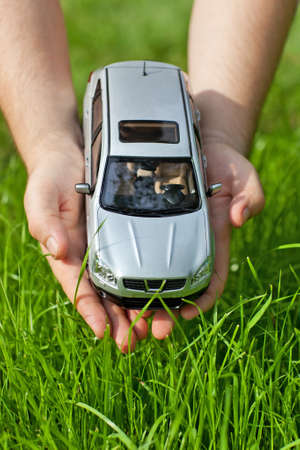 Hands with toy car on grass background. Stok Fotoğraf