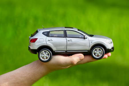 car side: Hand with toy car on grass background.