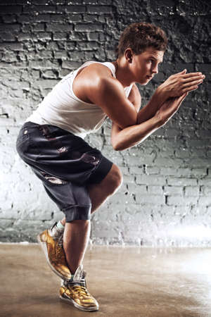 yoga man: Young man sports exercises. On wall background.