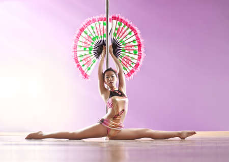 Young slim pole dance woman with fan. photo