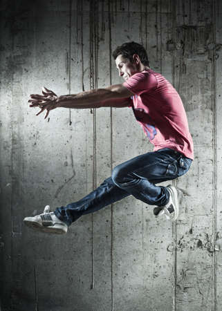 handsign: Young man dancer jumping. On wall background. Stock Photo