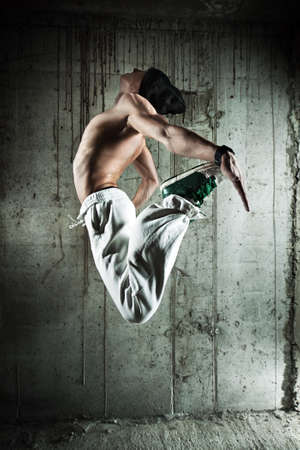 Young man dancer jumping. On wall background. photo