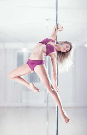 pole dance: Giovane donna pole dance. Colori brillanti bianchi. Archivio Fotografico
