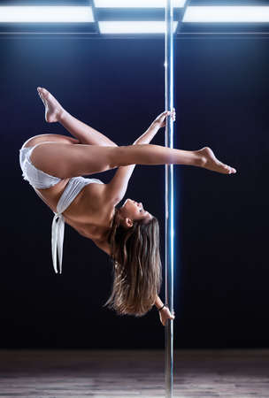 pole dance: Young strong pole dance woman.