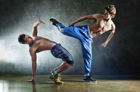 hombres haciendo ejercicio: Dos deportes de los hombres jóvenes luchando en la pared de fondo. Foto de archivo