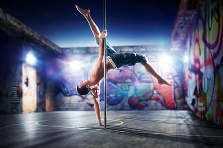 pole dance: Giovane uomo forte di ballo pole su sfondo urbano.