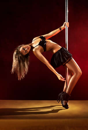 Young sexy pole dance woman. Red lights. photo