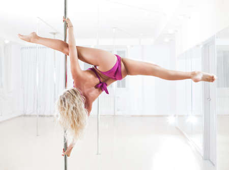 Young pole dance woman. Bright white colors. photo