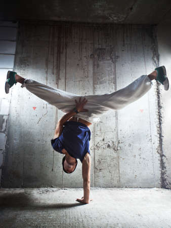 Young man break dance on wall background. photo