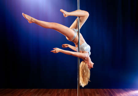 Young pole dance woman upside down. photo