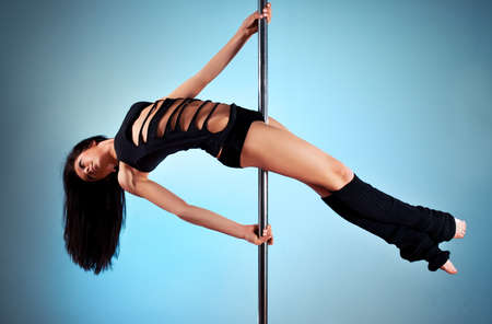 poledance: Young pole dance woman. On blue wall background.