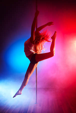 Young pole dance woman jumping. photo
