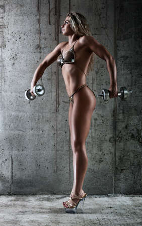 Young sexy muscular woman with dumbbell. photo