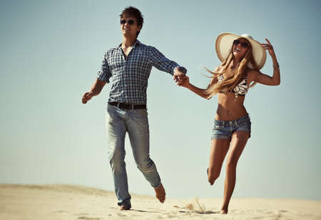 Young couple running on beach. photo