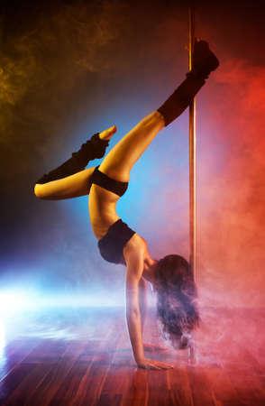 pole dance: Giovane danza donna pole con effetto fumo.